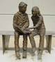 Sculpture outside of the library of a Boy and Girl reading on a bench